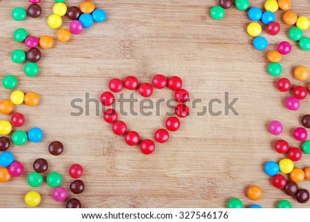 heart of red candies on a blackboard