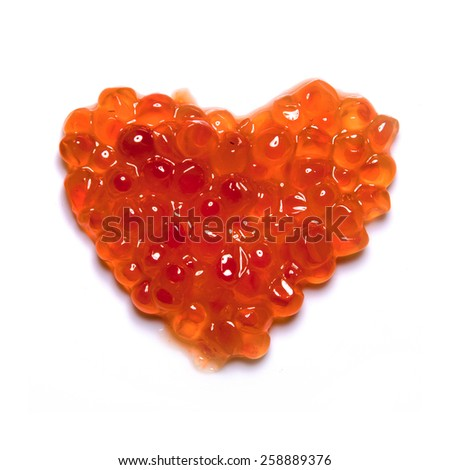 Heart of red caviar on a white background - stock photo