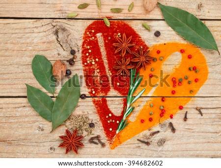 Heart of spices and seasonings. Turmeric, paprika, cumin, rosemary, garlic, cardamom, nutmeg, clove Bud, Bay leaf, star anise, green and pink pepper, juniper, coriander - stock photo