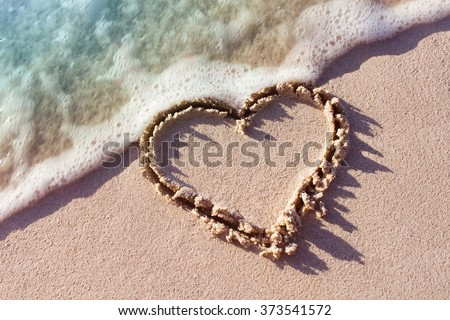 heart on a sand of beach with wave on background - stock photo