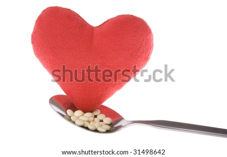 Heart on a spoon with tablets, shot on white background - stock photo