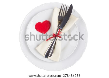 Heart on plate with fork and knife over white background
