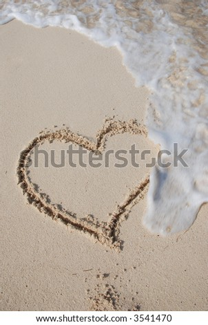 Heart on sand beach being washed away - stock photo