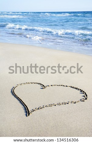 heart outline on the wet beach sand against sea wave - stock photo