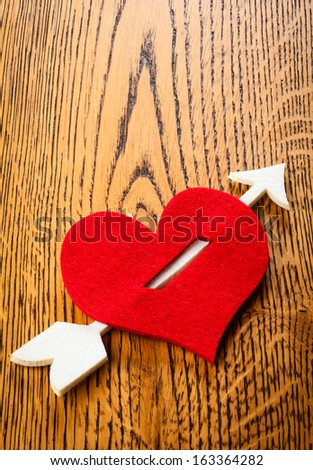 heart pierced by  cupid arrow on the wooden background - stock photo