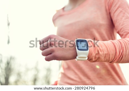 Heart rate monitor smart watch for sport. Athlete wearing heart rate monitor. Runner using sports smartwatch on running workout outside. Female athlete tracking activities using wearable technology. - stock photo