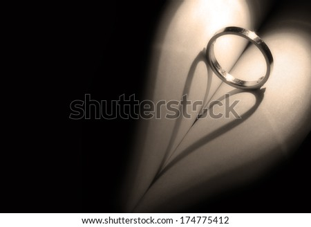 heart shadow with rings on a book middle write your text in black space with grain vintage - stock photo