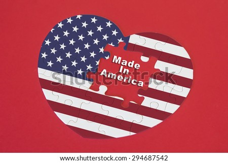 Heart shape America Flag jigsaw puzzle with a written word Made In America with red background - stock photo