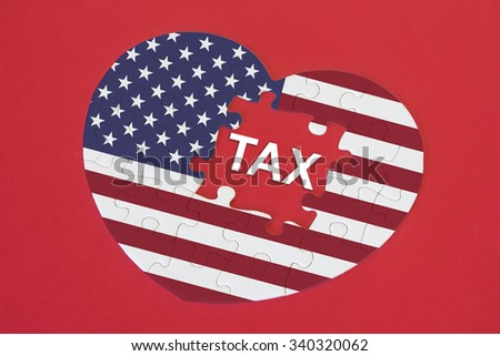 Heart shape America Flag jigsaw puzzle with a written word TAX with red background - stock photo