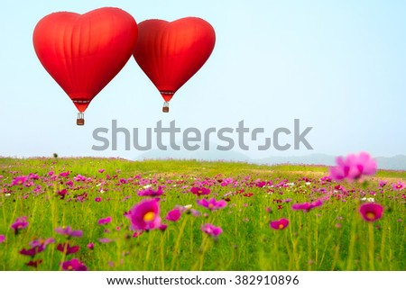 Heart shape ballooning flying over flower filed