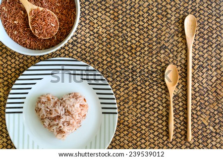 Heart shape brown rice with wooden spoon - stock photo