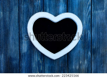 Heart shape chalkboard on the blue wooden wall - stock photo