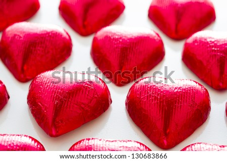 Heart shape chocolate candies on white background.