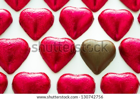 Heart shape chocolate candies wrapped in red foil for Valentine's Day. - stock photo