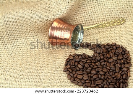 Heart shape coffee beans spilled from traditional Turkish copper coffee pot on a burlap - stock photo