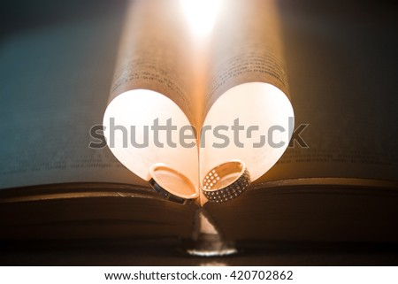 Heart shape formed in the pages of a book with two wedding rings inside lit by a warm light - stock photo