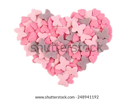 Heart shape formed with sugar hearts and butterflies isolated on white background. Love concept. Valentine's Day concept