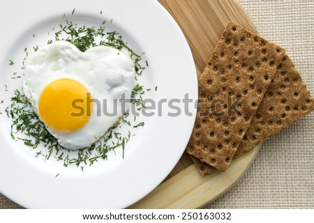 Heart shape fried egg in a white plate. With cutting board and crisp bread. - stock photo