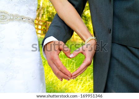 Heart shape is formed by the bride and groom putting their hands together while standing outside in a country field on their wedding day. - stock photo