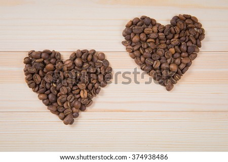 Heart shape made from coffee beans on wooden surface. coffee in the shape of a heart. Valentine's Day, concept of love. Two hearts of coffee.  - stock photo