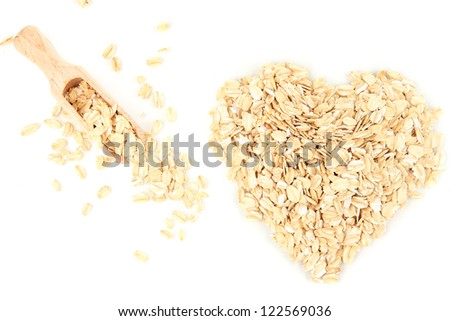 Heart shape made from oat flakes with wooden scoop isolated on white - stock photo
