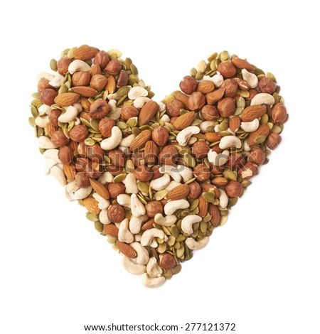 Heart shape made of multiple different nuts and seeds mix, composition isolated over the white background - stock photo