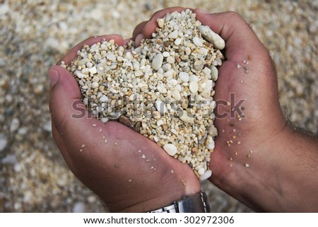 Heart shape made of pebbles in male hands wearing a wristwatch on beach. Having fun on a vacation. - stock photo