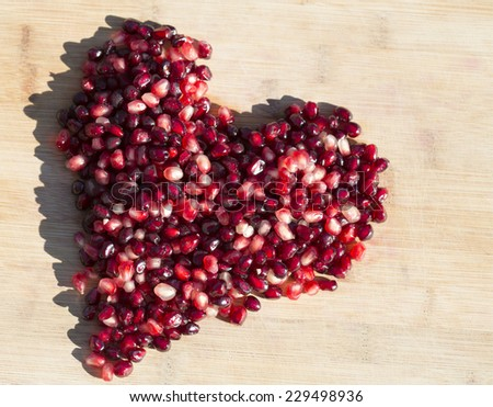heart shape made of pomegranate arils (seeds) with bamboo background - stock photo
