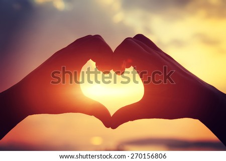 Heart shape making of hands against bright sea sunset and sunny golden way at water  - stock photo