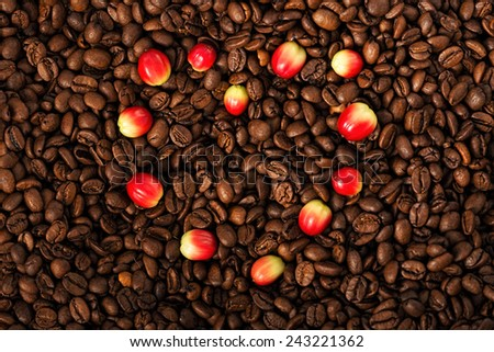 Heart shape of berries on aromatic coffee beans - stock photo