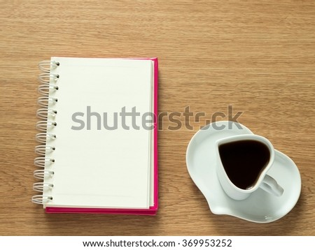 Heart shape of cup with coffee and heart shape of plate with opened book for diary. Love coffee. Top view. Happy Valentines Day background. - stock photo