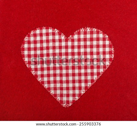 Heart shape on red wool background. Checkered tablecloth fabric heart sewed on red. - stock photo