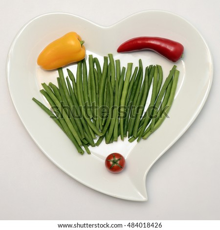 Heart shape plate of vegetables, healthy food on white background