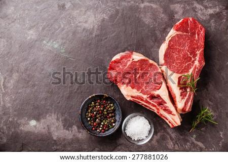 Heart shape Raw fresh meat Ribeye Steak with rosemary, pepper and salt on stone slate background - stock photo