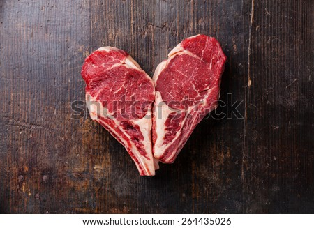 Heart shape Raw meat Ribeye steak entrecote on wooden background - stock photo