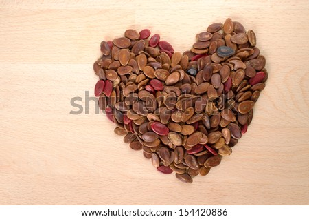 Heart shape red roasted watermelon seed on wooden cut board