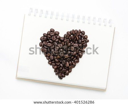 Heart shape roasted coffee beans on white notebook background. - stock photo