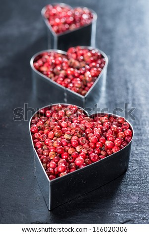 Heart shape with Pink Peppercorns on dark background (I Love Herbs Concept) - stock photo