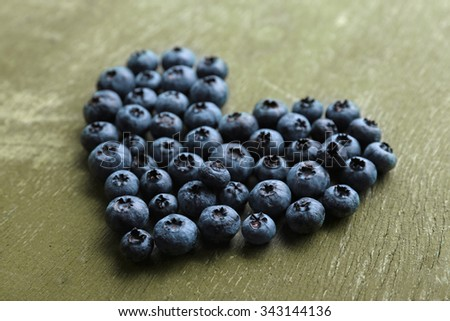 Heart shaped bilberries on old wooden background - stock photo