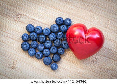 Heart shaped blueberries on wooden background. Tasty blueberries are antioxidant organic superfood.  - stock photo