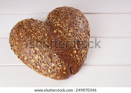 heart shaped bread for Valentine's day on white wooden board with copy space - stock photo