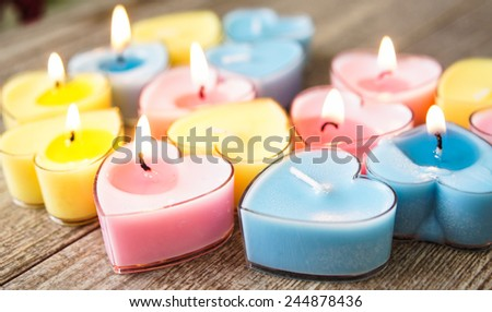 Heart shaped candles on the wooden background