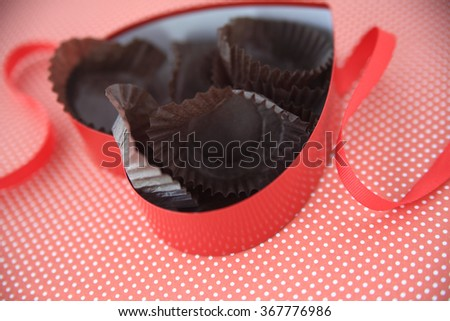Heart-shaped candy box with empty wrappers inside on polka dot background with red ribbon - stock photo
