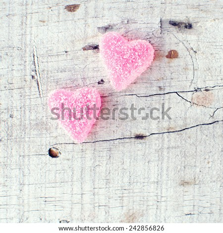 Heart shaped candy on wooden background