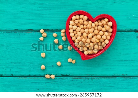 Heart shaped ceramic bowl with chick peas - stock photo