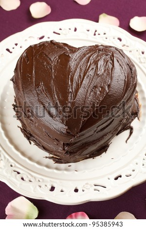 heart shaped chocolate cake in a traditional dish over a purple table cloth decorated with rose petals - stock photo