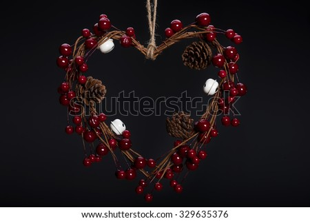 Heart shaped Christmas decoration with pine cones on dark background  - stock photo