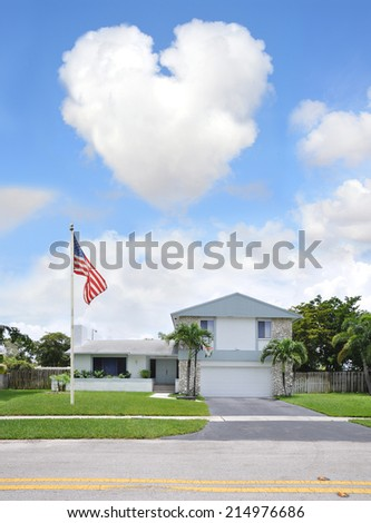 Heart shaped Cloud over Suburban Back Split Style home with Betsy Ross American Flag pole in residential neighborhood USA Blue Sky Clouds - stock photo