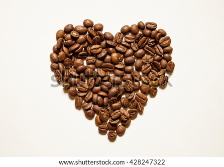 Heart shaped coffee beans on a white background. - stock photo