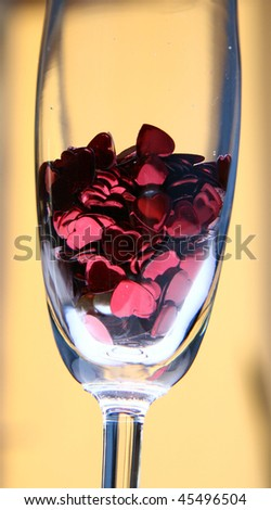 Heart shaped confetti in a champagne flute in close up on worm yellow background
